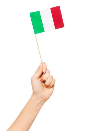 Hand holding and raising small paper Italian flag