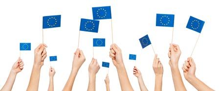 Handen die vlaggen van de Europese Unie houden en verhogen