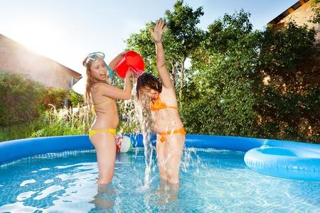 Nette Freunde Wasser über sich selbst im Pool Gießen Standard-Bild - 72464233