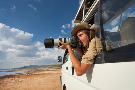 지프의 열린 창에서 사진을 찍고있는 관광객 스톡 콘텐츠