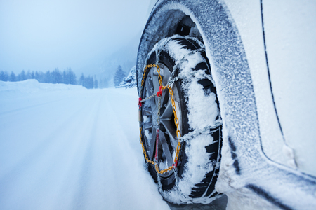 Car with snow chains for tire on snowcapped road