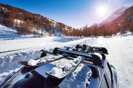 Snow-covered skis fastened on car roof rack Standard-Bild