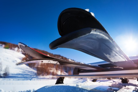 Skis sur les rails de toit de voiture contre le ciel bleu
