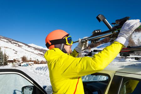 Porträt des aktiven männlichen Skifahrers, der Skier an Dachreling des Autos an schneebedeckten Bergen befestigt Standard-Bild