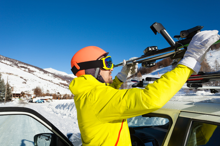 Portrait of active male skier fastening skis to roof rails of car at snowy mountains