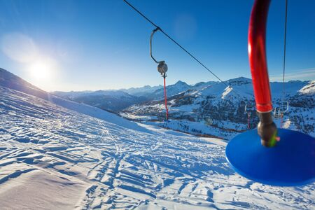 Close-up picture of empty blue button lift against beautiful mountain scene at sunny day Stock Photo