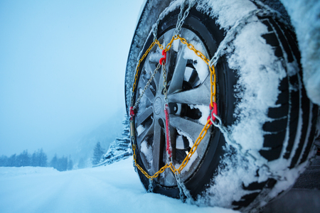 Close-up picture of automobile wheel with ice chains for tires on the snow-covered road Imagens