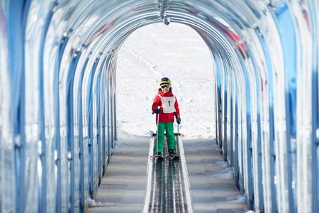 스키 리프트를 사용 하여 투명 한 안전 아치 밑의 통로 오르막가 행복 한 아이 소년의 초상화 스톡 콘텐츠