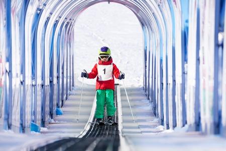 스키 리프트를 사용하여 투명 안전 아치 밑의 통로에서 오름차순 어린 소년