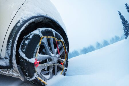 Wheel with snow tire chains on mountain road Imagens