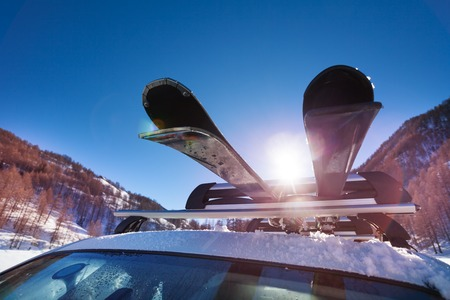 Car roof with two pairs of skis on the rack Stock Photo