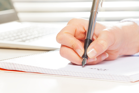 Female hand with fountain pen writing on notebook