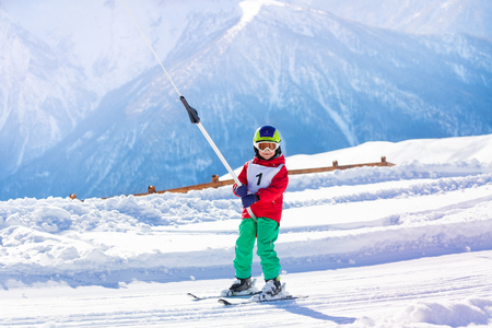 kids at the ski lift: Young skier using a surface lift on the slope