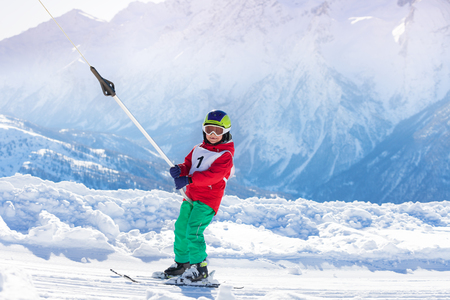 kids at the ski lift: Portrait of boy using a button lift on the slope