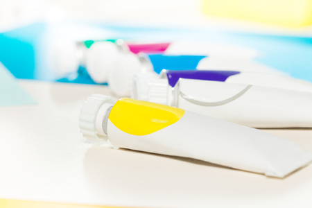 Tubes of multicolored oil paint with copy-space
