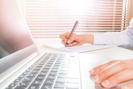 payload: Womans hands using laptop and writing on notepad Stock Photo