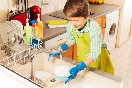 Nice boy wash dish in sink under water from tap