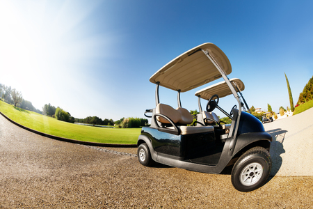 Car park with two golf-carts at sunny day