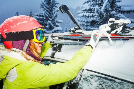 Female skier fastening skis to roof rails of car