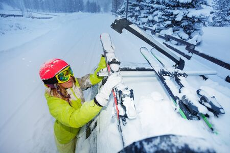 Female skier fastening skis to car roofs rails