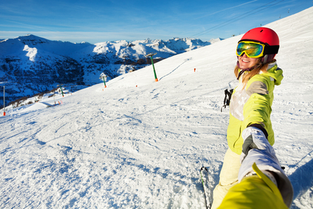 Smiling female skier taking selfie against slope Stock Photo