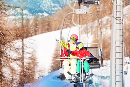 kids at the ski lift: Active woman and her kid son lifting on chairlift Stock Photo