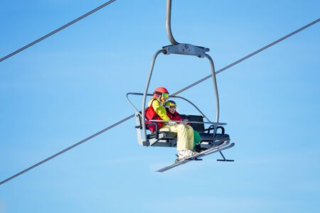 kids at the ski lift: Two skiers lifting on chairlift against blue sky