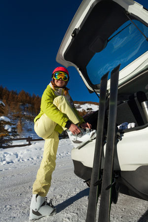 Smiling female skier putting her ski boots on Фото со стока