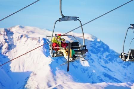 Twee skiërs die op de lift heffen tegen besneeuwde bergen