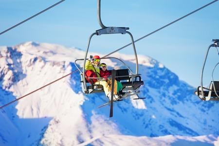 Two skiers lifting on lift against snowy mountains Stock fotó