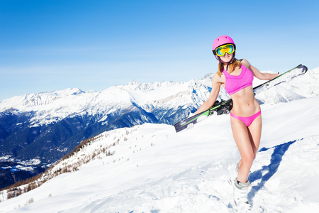 Girl in sports bra standing with skies behind back Фото со стока - 76754628