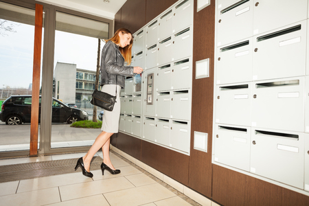 addressee: Young woman closing her mailbox in the hall