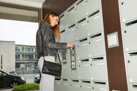 addressee: Young pretty woman closing her mailbox with a key