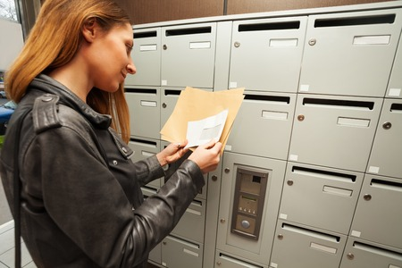 addressee: Woman holding envelopes with copy-space at a hall