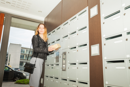 addressee: Happy woman taking package out mailbox at doorstep