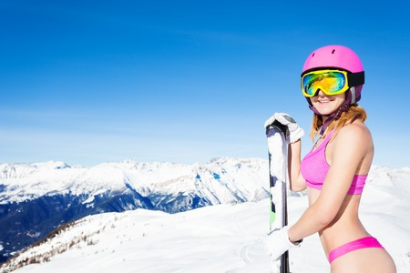 Attractive undressed girl with ski in mountains