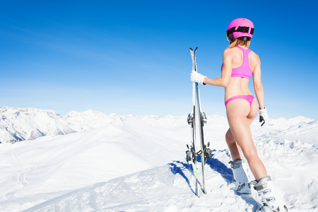 Vrouwelijke skiër staande in bikini op berghelling Stockfoto - 76754641