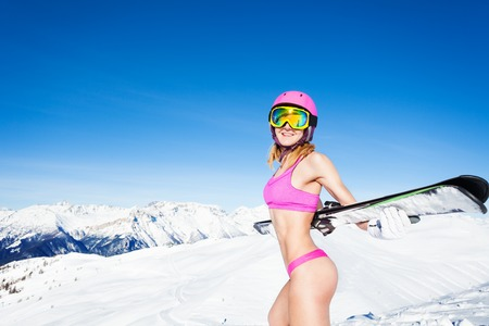 gstring: Woman in bikini standing with skis on a snowy peak