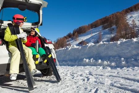 Gelukkige skiërs die warme thee van thermosflessen drinken Stockfoto - 76754650