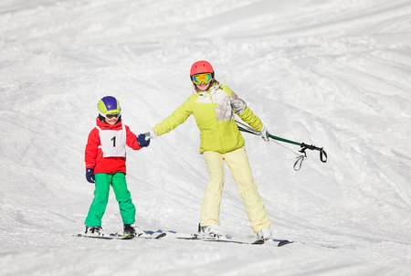 Active mother teaching son skiing holding hands