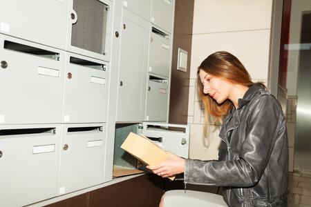 Vrij jonge vrouw die pakket van brievenbus neemt