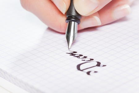 Hand writing with fountain pen on squared notebook Stock Photo