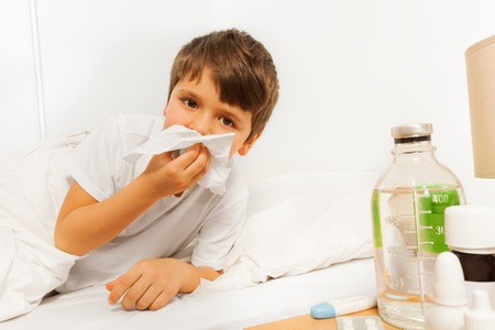 snivel: Sick kid boy blowing his nose with a napkin