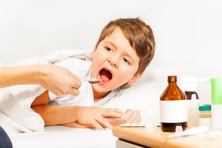 rheum: Sick Caucasian kid boy taking meds laying in bed Stock Photo