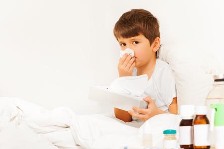 ベッドに座っていると、紙ナプキンを使用して病気の男の子