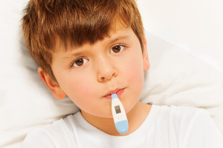 Boy taking temperature with electronic thermometer