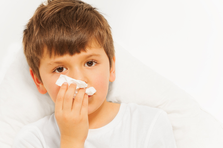 snivel: Sick kid boy with bad cold using paper napkins