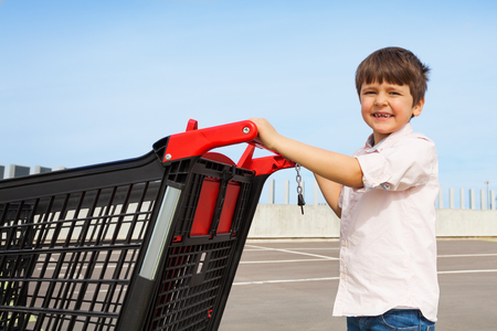 Smiling boy pushing shopping cart to supermarket Stock Photo