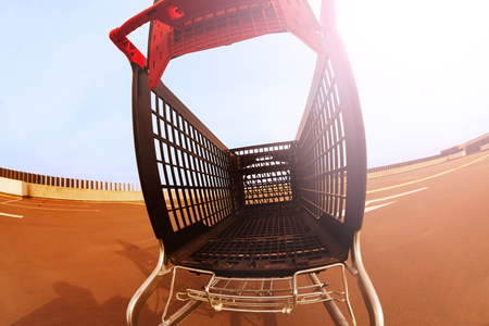 Shopping cart standing at open rooftop parking Stock Photo