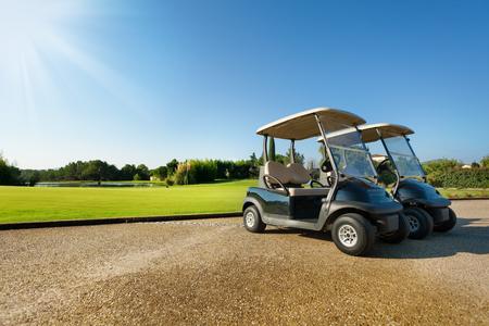 夏の駐車場に立っている 2 つのゴルフカート 写真素材